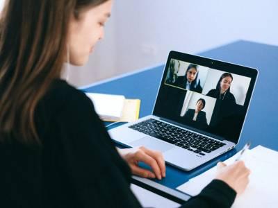 Eine Frau am MacBook, in welcher eine Videokonferenz mit drei anderen Personen läuft