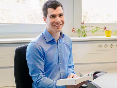 Ein junger Mann der am Schreibtisch sitzt und in die Kamera lacht