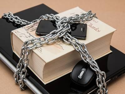 Laptop, Buch und Smartphone mit einer dicken Eisenkette zusammengekettet