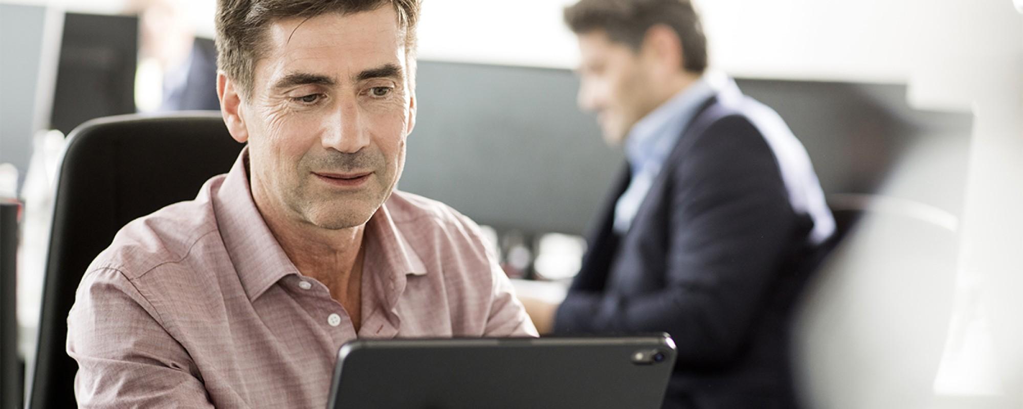 Ein Mann, welcher an einem iPad arbeitet.