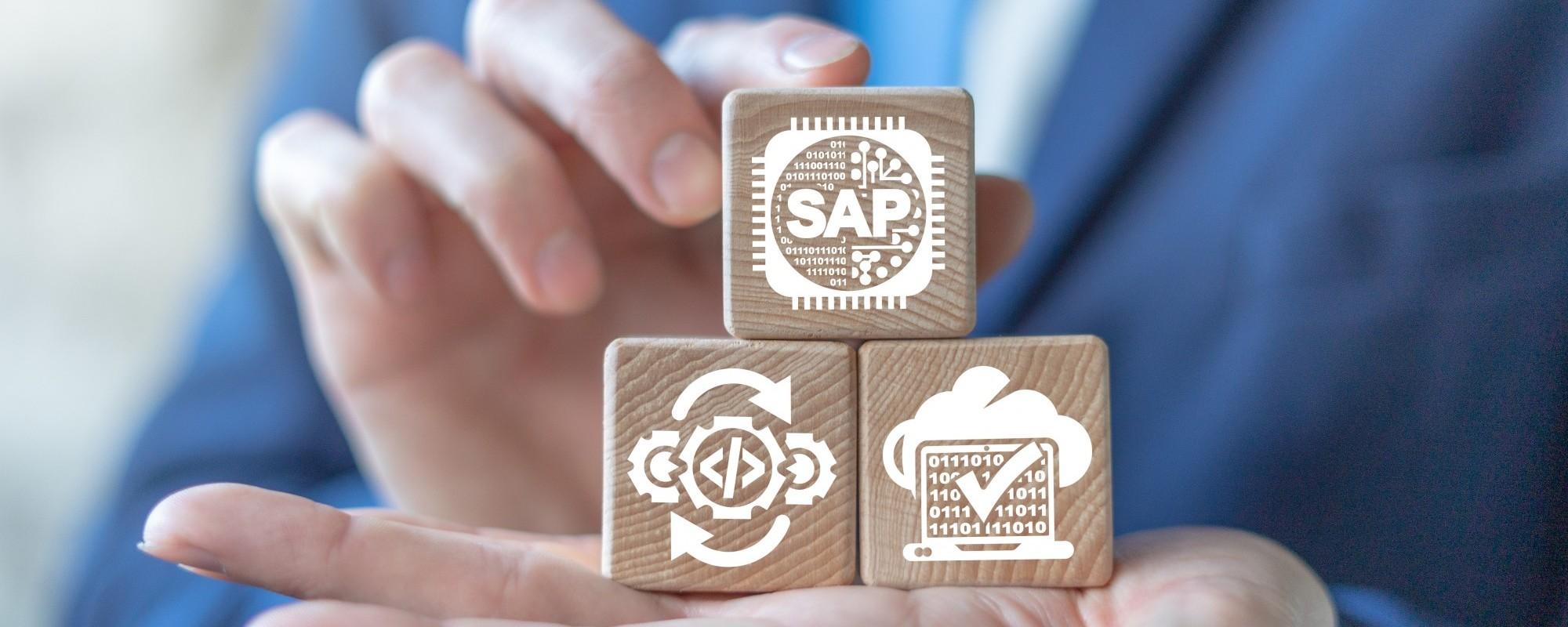 Eine Nahaufnahme von einer Hand auf welcher sich Holzblöcke befinden welche mit SAP Logos bedruckt wurden.