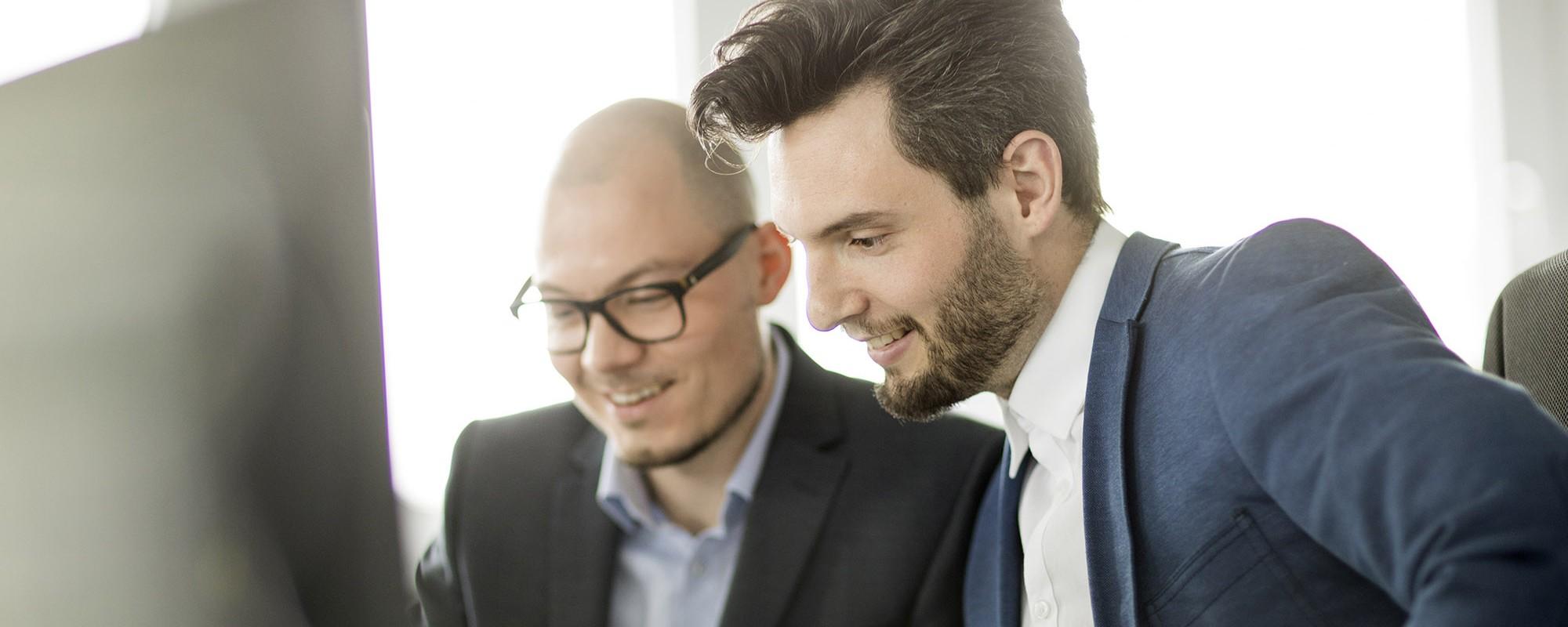 Zwei Männer in Anzügen, welche vor einem Bildschirm sitzen und etwas besprechen.